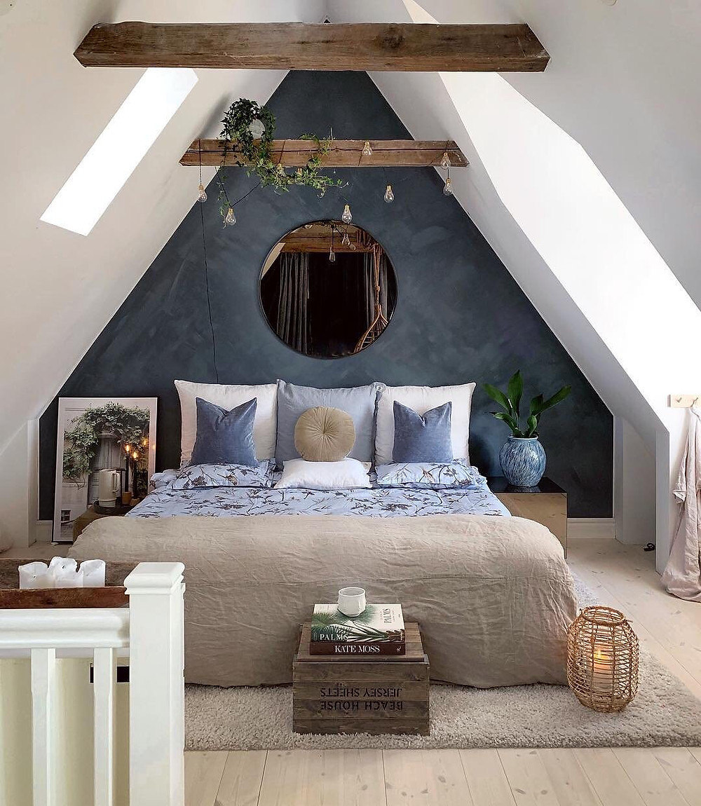 cozy attic bedroom with blue walls and circle mirror