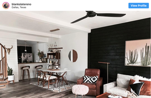 Black accent wall in the living room next to a white dining room table and chairs with wooden legs