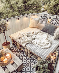 cozy outdoor space with tile flooring, sofa seating and plants and pillows