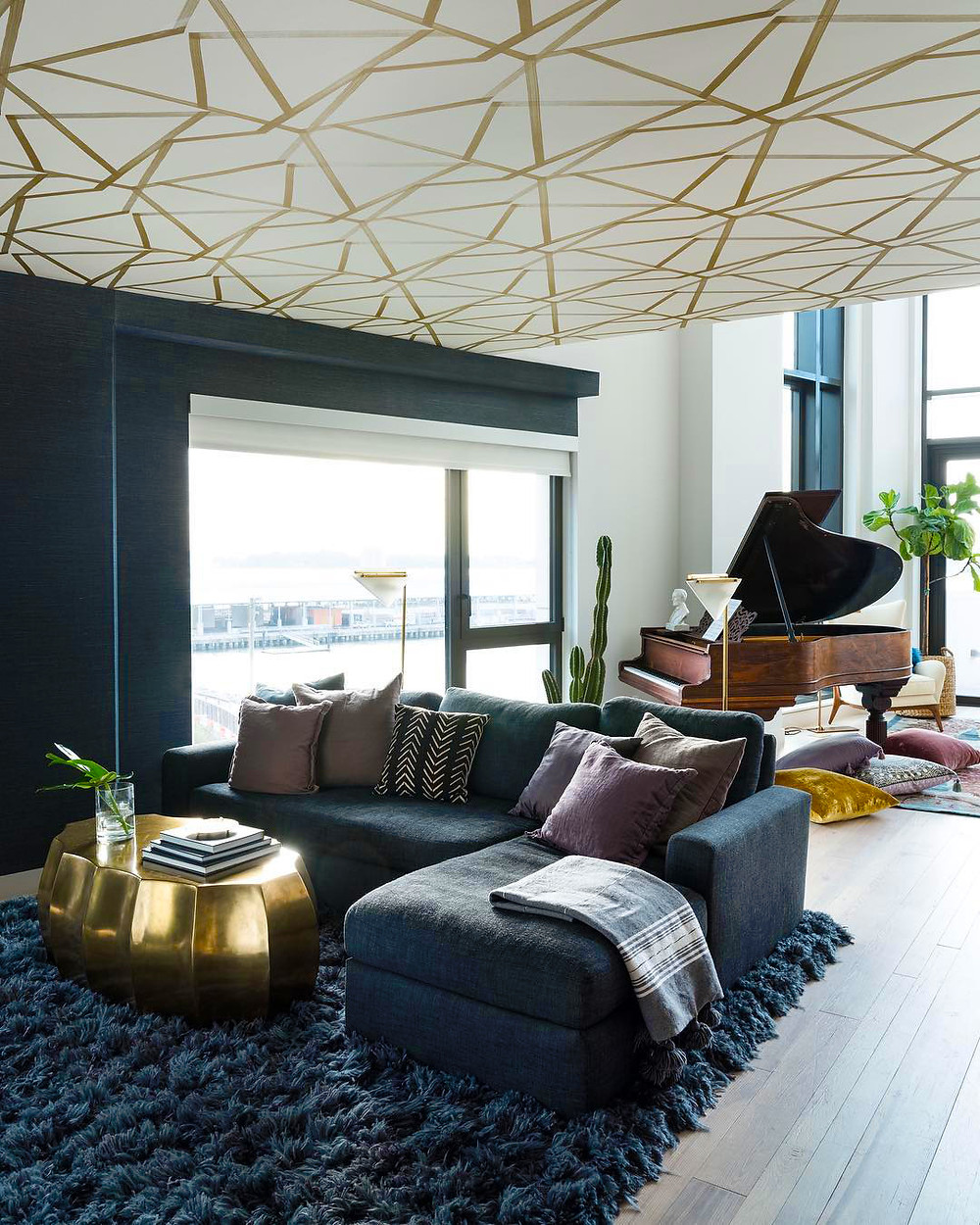 luxury living room with blue shag rug, blue sofa, and golden accent touches