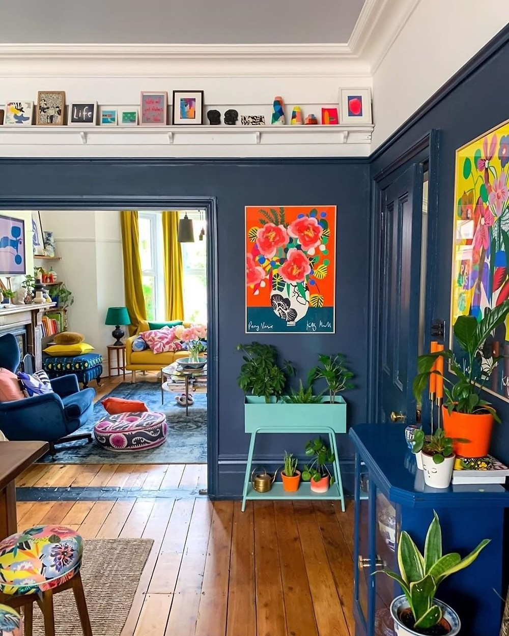 Colorful eclectic living room with blue walls and tons of artwork