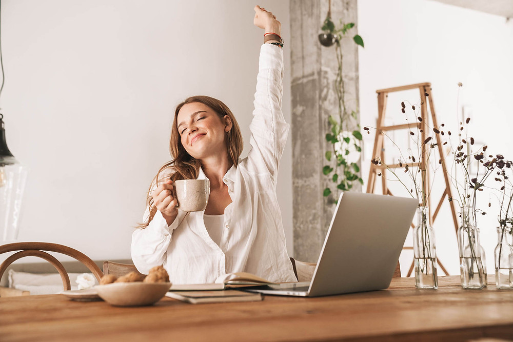 image of young redhead business woman sitting indoors in office stretching drinking coffee