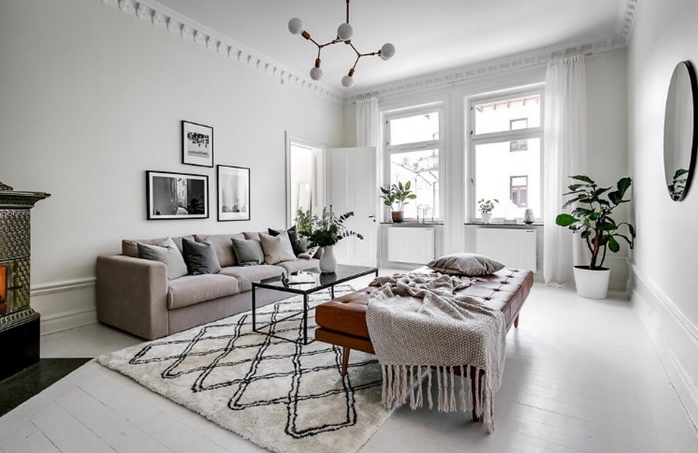 Scandinavian interior design living room with white walls, tan-colored sofa, and large leather ottoman seat