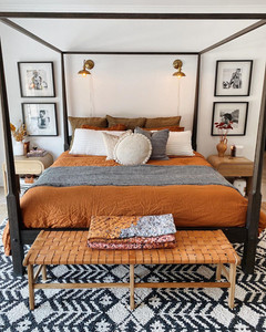 autumn bedroom colors with orange bed sheets and black canopy bed
