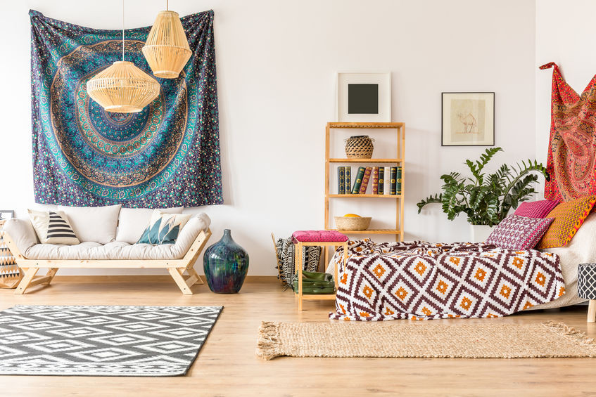 Boho home decor bedroom with a sofa, bed, rugs, and colorful tapestries