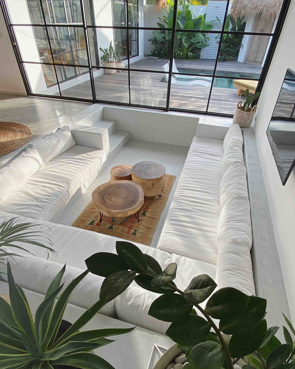 Luxurious living room interior design with huge white sectional sofa and tribal rug