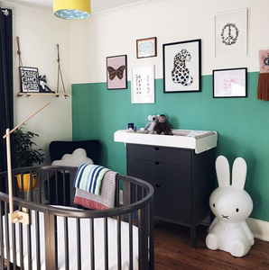 Teal and white wall with black chair, changing table, and crib in baby nursery room