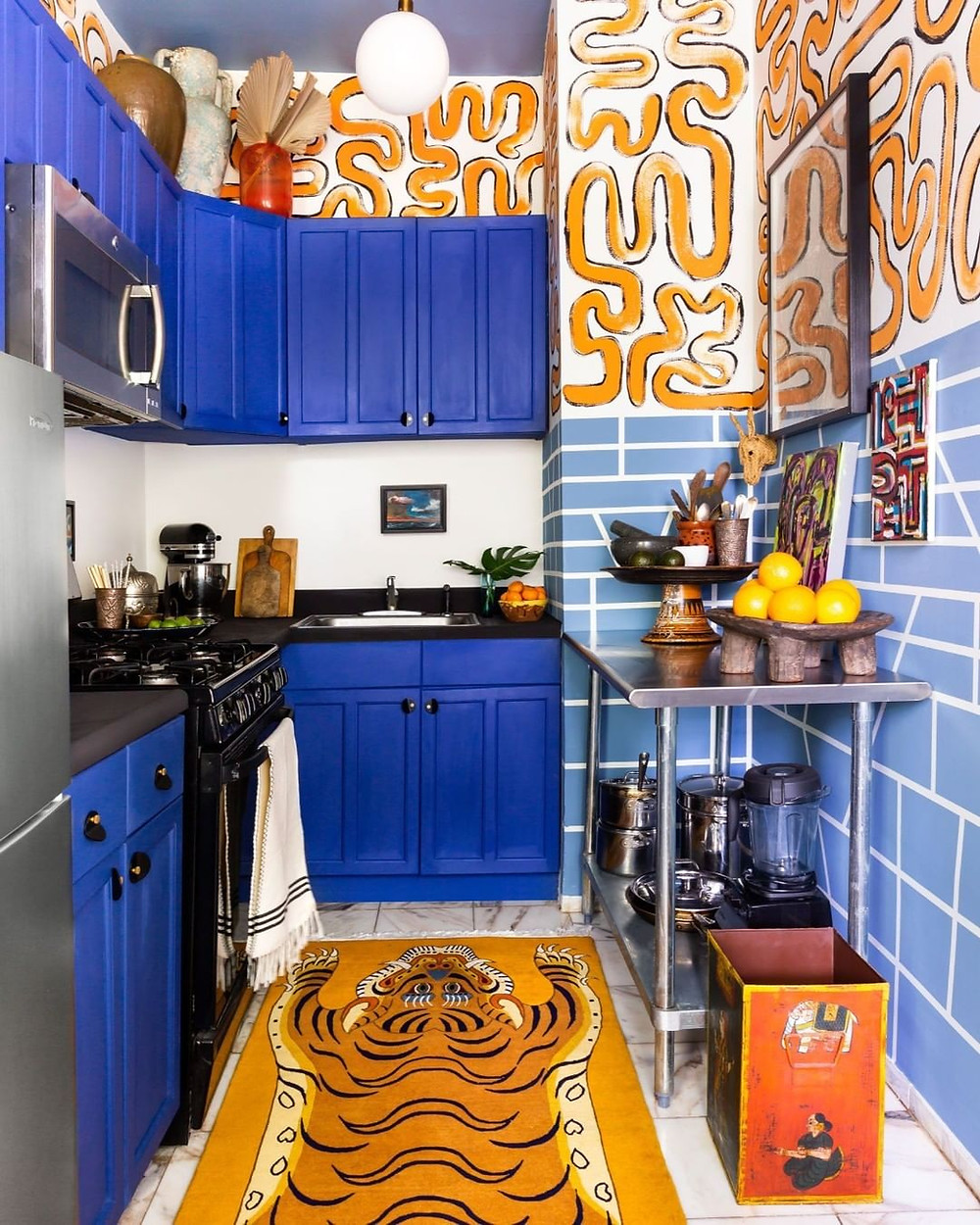 bold and colorful kitchen design with blue cabinets, tiger rug and orange pattern wallpaper