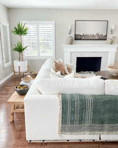 large white sectional and hardwood floors with teal blanket