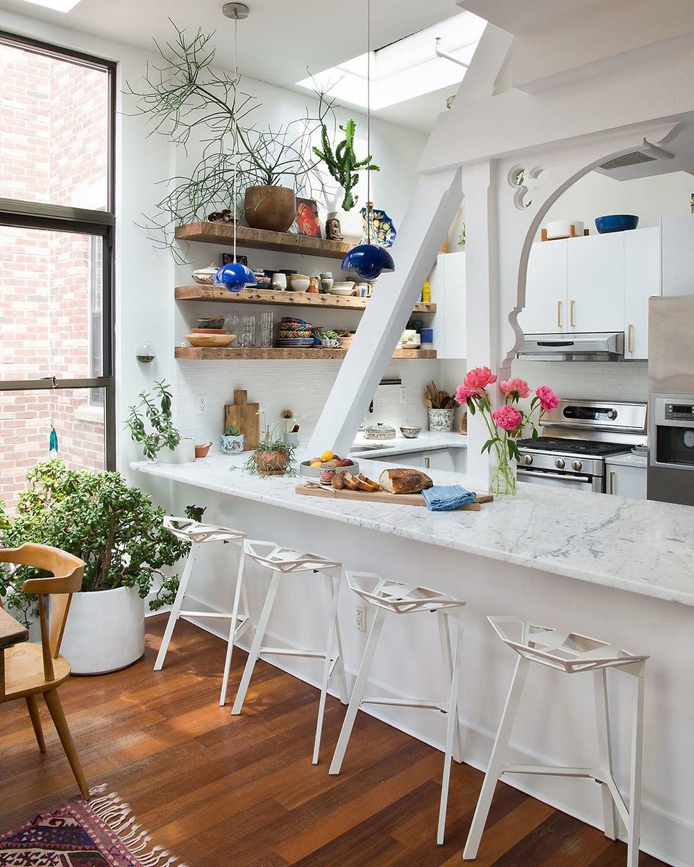 white kitchen with wooden flooring and shelves decorated with food and appliances