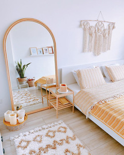 bright boho bedroom with large wooden floor mirror