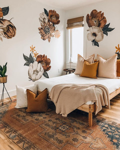 flower wallpaper in bedroom decorated for fall with orange colors and tribal rug