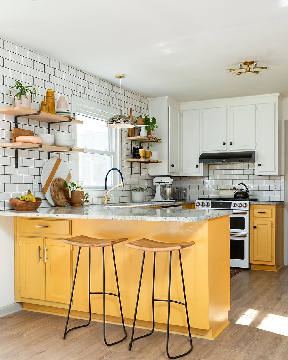 Nice kitchen decor with yellow cabinet colors and marble countertops and subway tiles