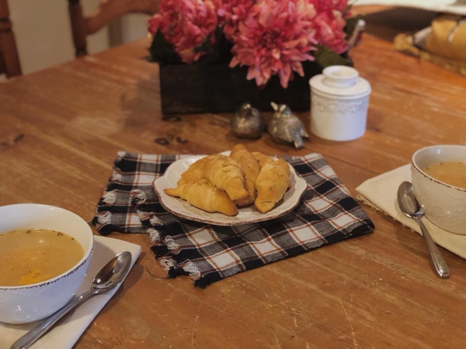 Homemade goat cheese filled Pillsbury crescent rolls with seasoning. Warm, cozy table setting with plaid napkins, salt and pepper shakers, butter crock. Flowers centerpiece. Two bowls of homemade soup.