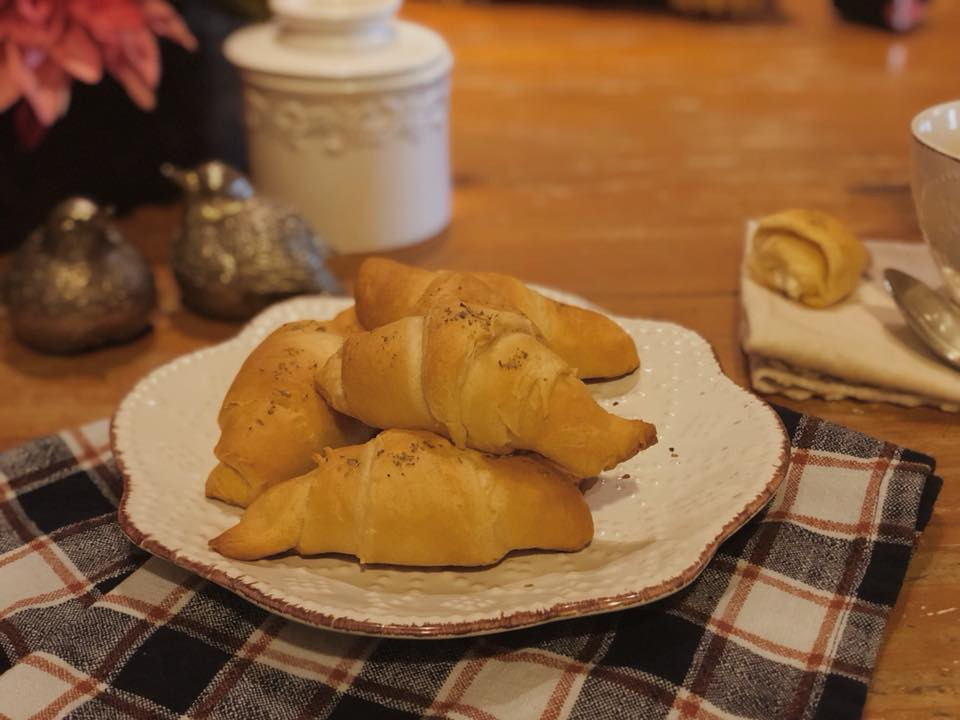 Homemade goat cheese filled Pillsbury crescent rolls with seasoning. Warm, cozy table setting with plaid napkins.
