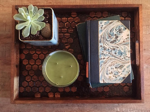 Handmade wooden tray with honeycomb pattern design. Green home decor items. Succulent, candle, and books displayed on tray.