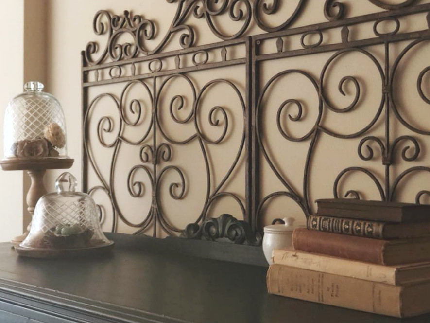 Iron gates. Cozy home decor. Credenza with books, vases, and other decorations.