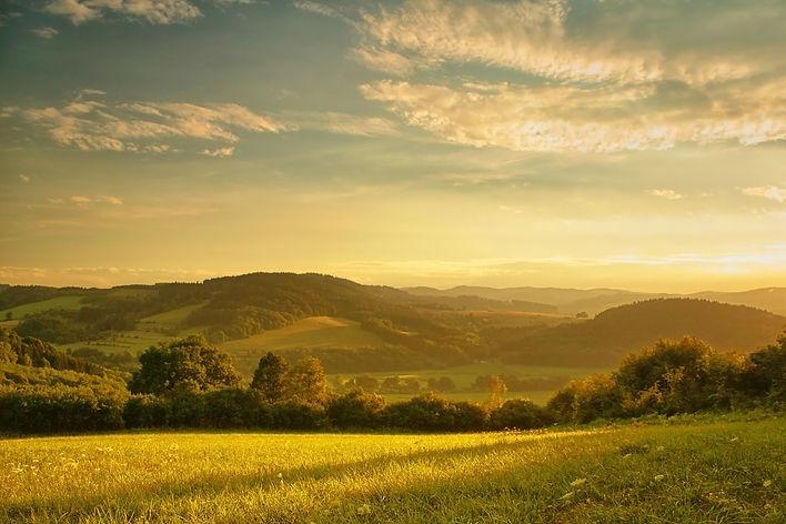 Sunset over hilly landscape, the golden