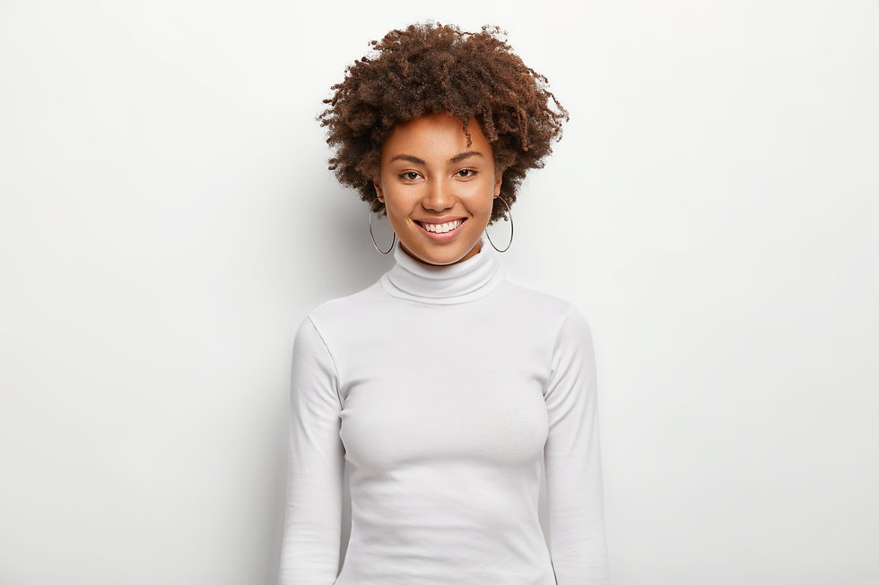 Photo of charismatic lovely woman with curly hair, has fun, toothy smile on face, satisfie