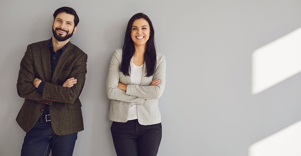 A businessman and a business woman are standing against a gray wall_edited.jpg