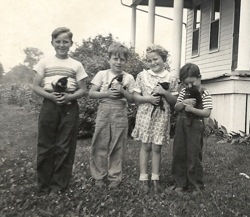 Janet with her brothers and the farm cats