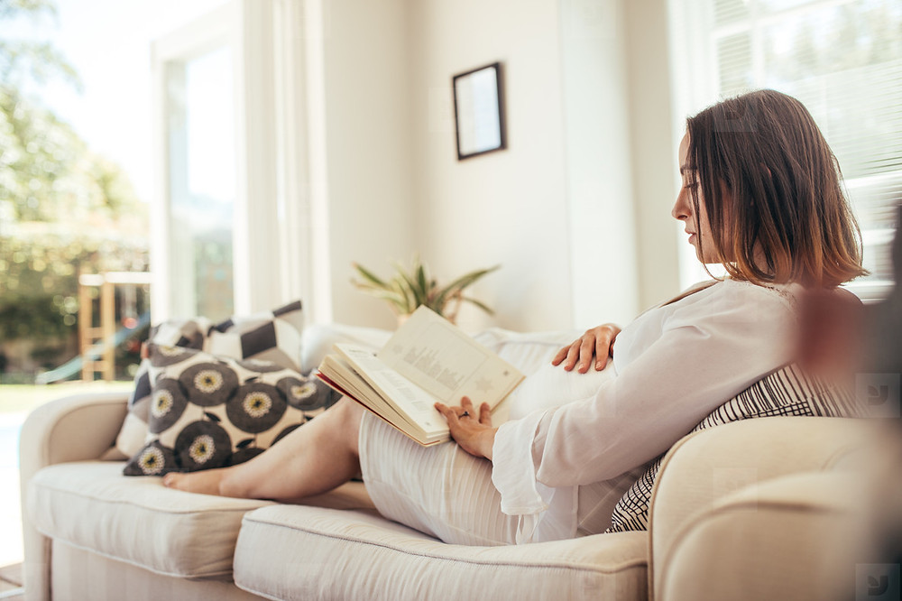Pregnant woman relaxing at home on the sofa with a book.