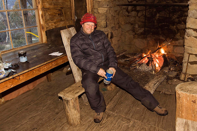 Michael Scott Lees Photographer at in front of a fire place inside Wheelers Hut in the Kosciuszko National Park