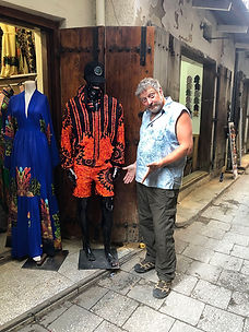 Michael Scott Lees Photographer looking quizical in front of clothing shop in Stone Town on Zanzibar Island
