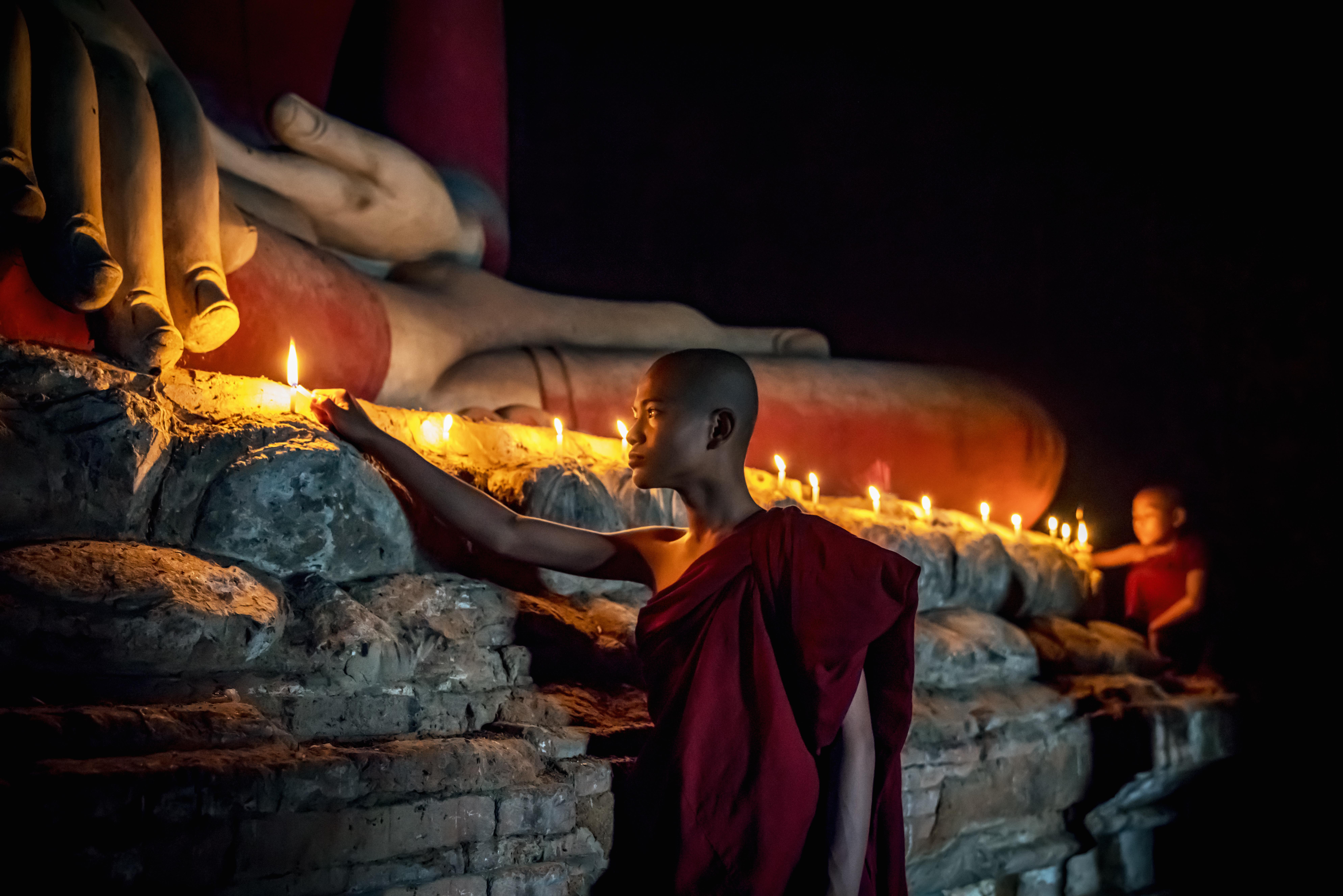Buddhist Monk Lighting Candles