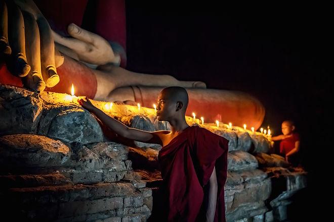 Buddhistischer Mönch, der Kerzen beleuch