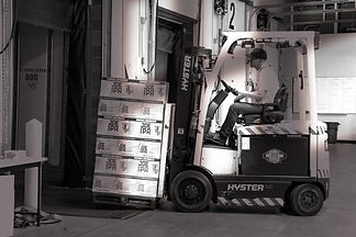 man-riding-a-yellow-forklift-with-boxes-