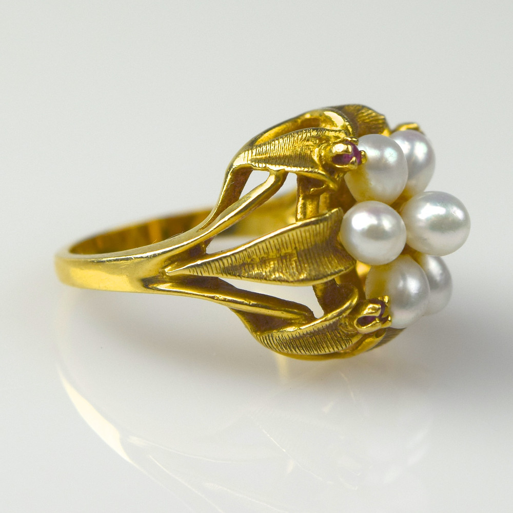 Gold ring with pearls on reflective background