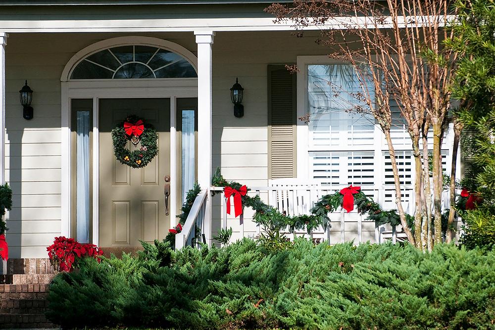 Decorar un jardín en Navidad con lazos rojos