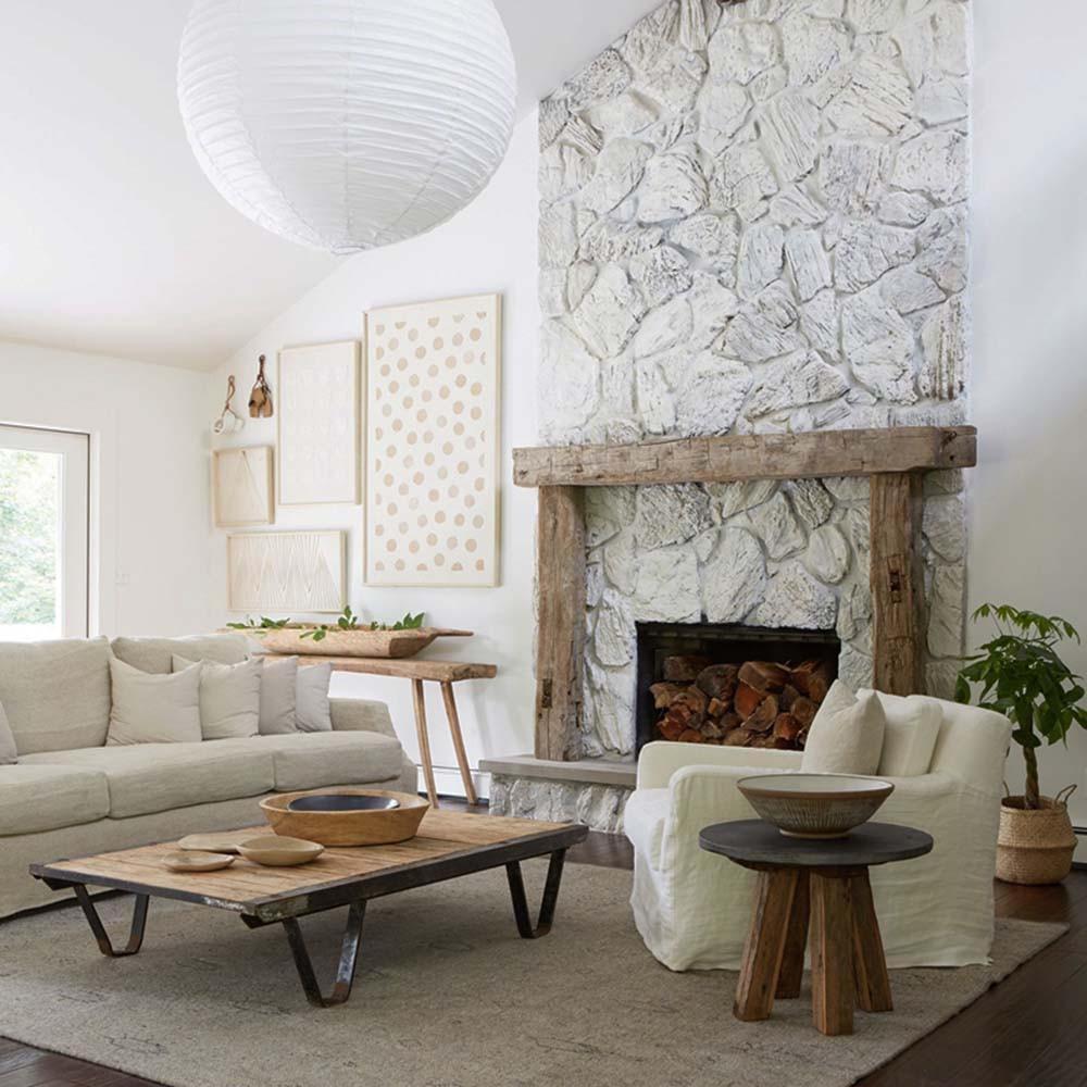 Chimenea revestida de piedra irregular y pintada de blanco
