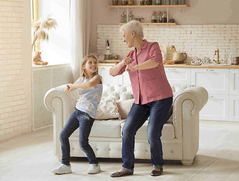 lady and granddaughter dancing at home.j