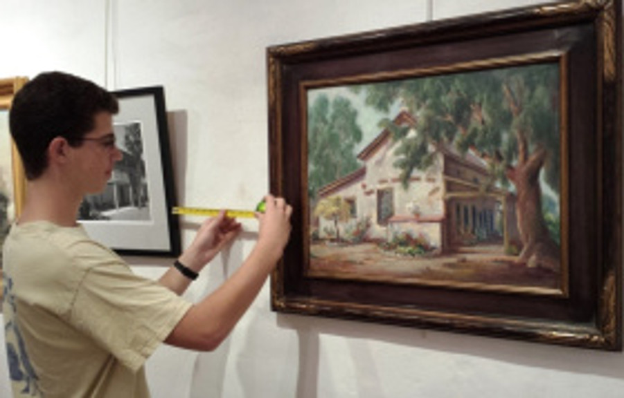 Volunteer Sam Majewski checks measurements while hanging the artwork. Photo by Anne Petersen.
