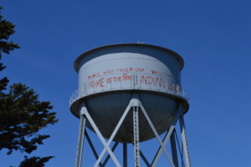"""Political Statements painted on the Water Tank recently """"Restored"""" to commemorate the occupation of the Island by the Indians of All Tribes. Photo by Mike Imwalle."""