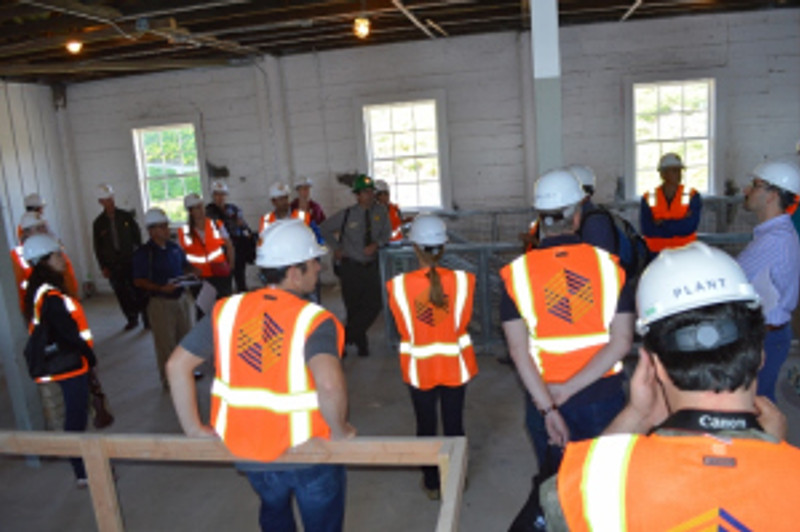 Historical Architect Jason Hagin (center) with group discussing ongoing seismic retrofit and rehabilitation of the Quartermaster's Warehouse. Photo by Mike Imwalle.