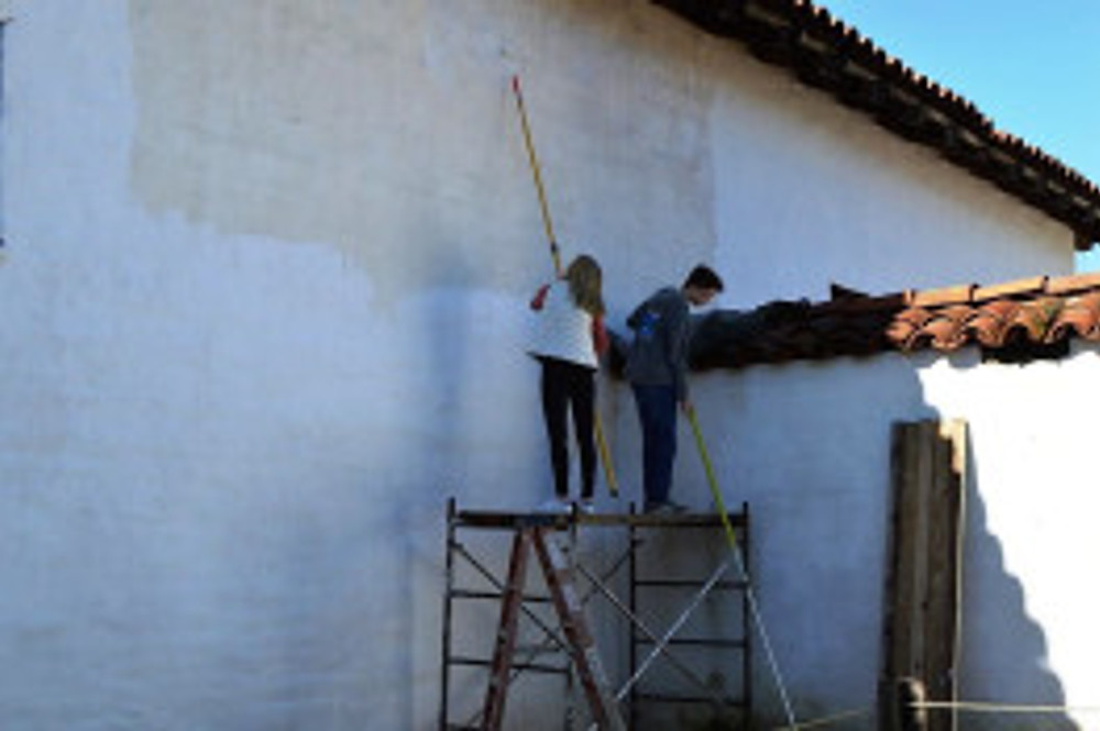Students whitewashing the last section of the exterior of the Presidio Chapel. Photo by Mike Imwalle.