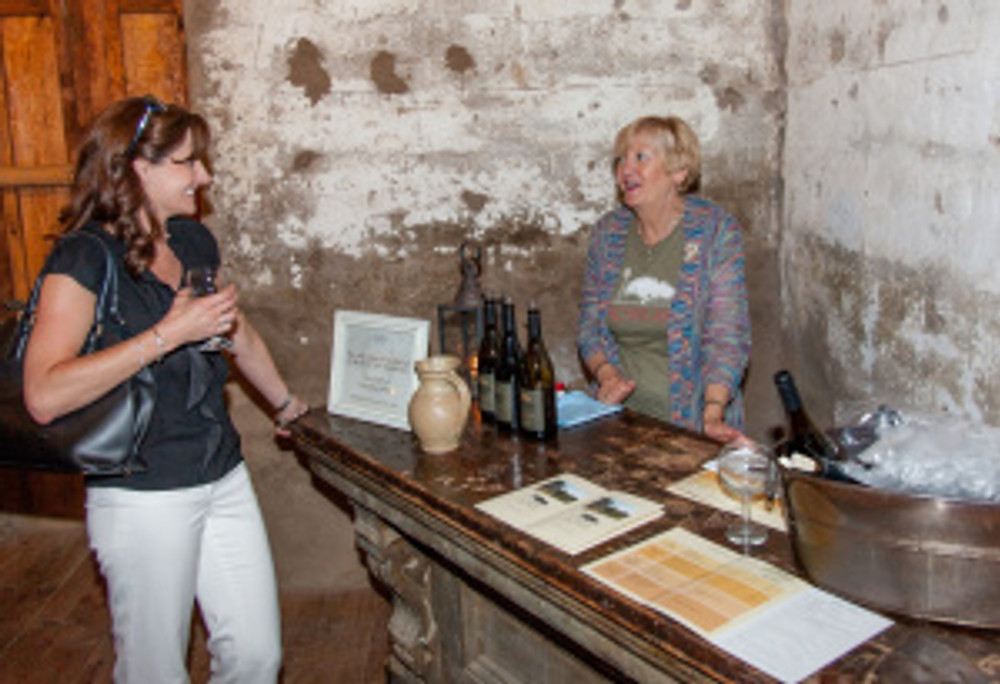 Wine pourer Norma sharing some of Roblar's vintages with a guest in la bodega. Photo by Friz Olenberger.