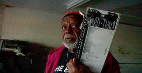"""A Black man holds up an historical document ruined by Hurricane Katrina in Brent Joseph's film """"A Loud Color"""""""