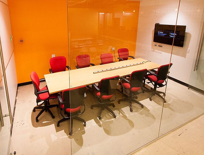 A conference room set up with a table, chairs, and TV monitor