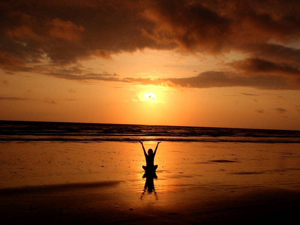 Beautiful sunset on the beach and meditated woman