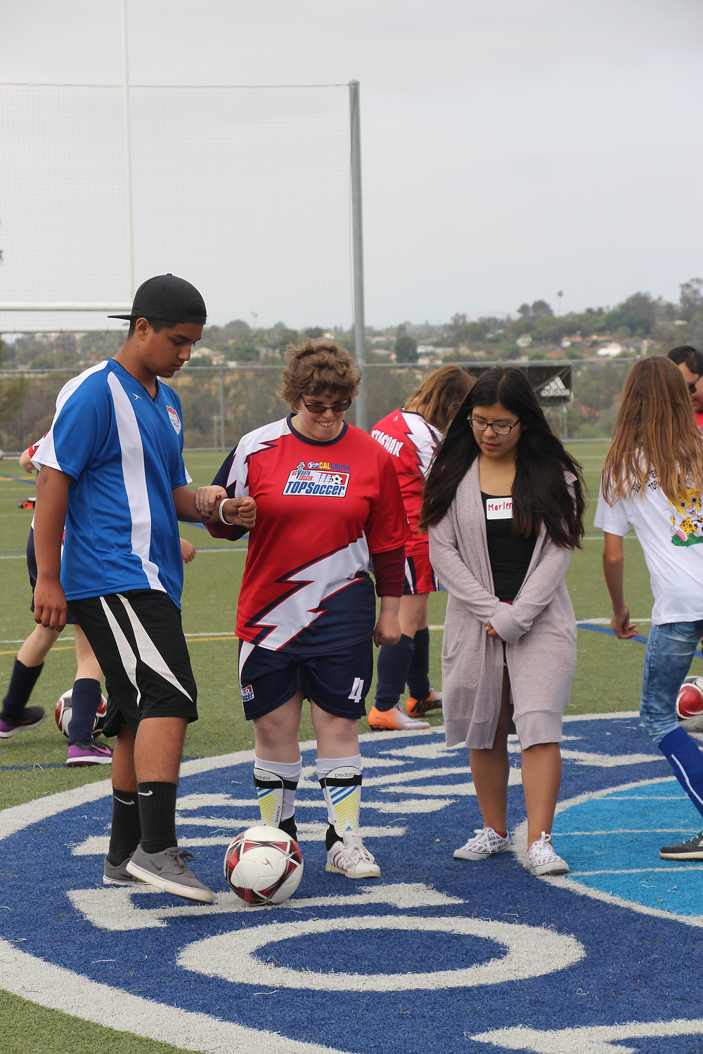 Luis helps a Vista athlete dribble during an exercise.