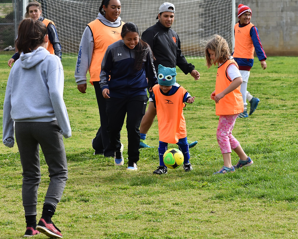 TOPSoccer's youngest member Amaya is encouraged to dribble downfield by SeaLion midfielder Elissa Magracia.