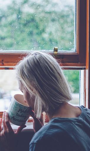 Mulher segurando uma caneca e olhando pela janela