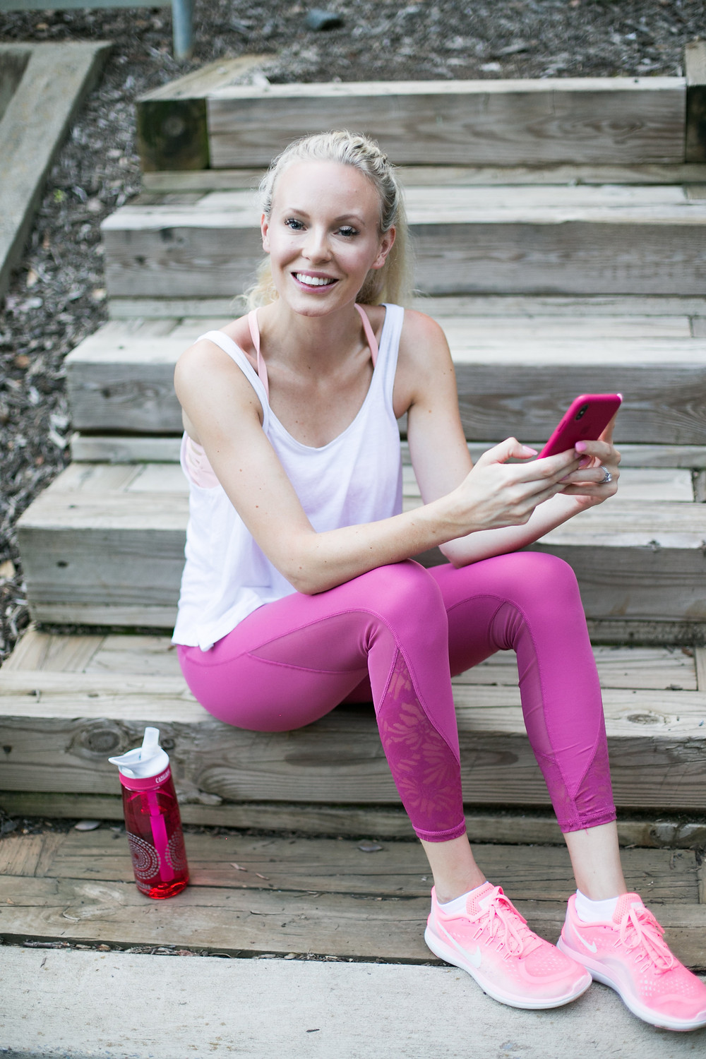 blonde fitness girl in pink leggings with iphone