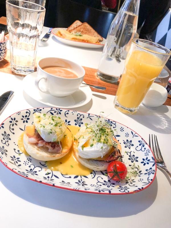 eggs benedict breakfast with coffee and orange juice