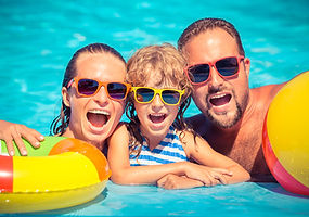 Happy family playing in swimming pool. S