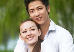 Attractive Asian Couple hugging in park_